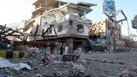 FILE PHOTO: People walk past a building destroyed during recent fighting in Yemen's southwestern city of Taiz © Anes Mahyoub