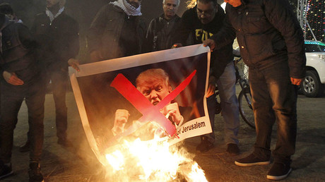 Palestinian protesters burn pictures of US President Donald Trump at the manger square in Bethlehem on December 5, 2017. © Musa Al Shaer