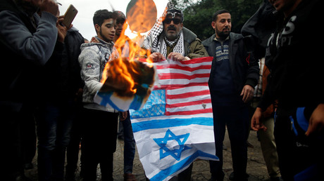 Palestinians burn signs depicting an Israeli flag and a U.S. flag during a protest in Gaza City on 6 December, 2017  © Reuters/Mohammed Salem