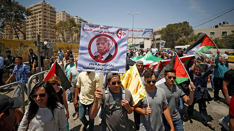 A Palestinian demonstrator holds an anti-U.S. President Donald Trump poster during a protest in support of Palestinian prisoners on hunger strike in Israeli jails, near Qalandiya checkpoint near the West Bank city of Ramallah May 22, 2017. © Reuters