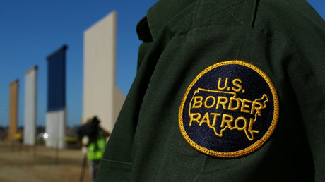 A border patrol officer stands next to some of Donald Trump's border wall prototypes along the US-Mexico border on October 23, 2017. © Mike Blake