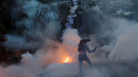 A Palestinian demonstrator hurls back a tear-gas canister fired by Israeli troops © Mohamad Torokman