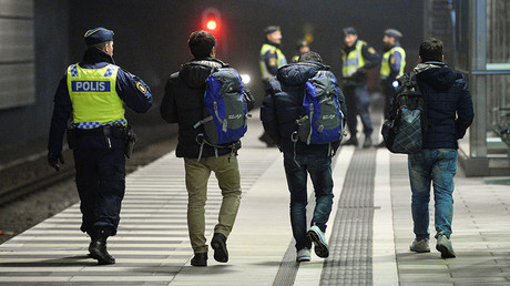 FILE PHOTO: A police officer escorts migrants from a train at Hyllie station outside Malmo, Sweden. © Johan Nilsson