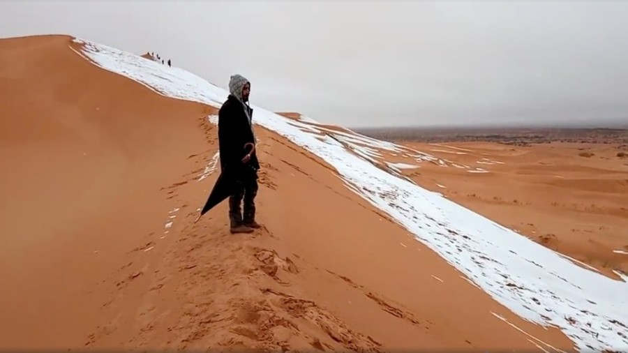 Snow paints red sand dunes of Sahara desert a wondrous white