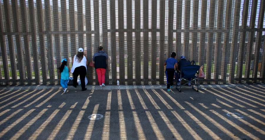 People hold conversations through the US Mexico border wall at Border Field State Park in California
