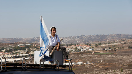 A boy sits atop the roof of a vehicle at the entrance to the Jewish settler outpost of Amona in the West Bank, October 20, 2016 © Ronen Zvulun