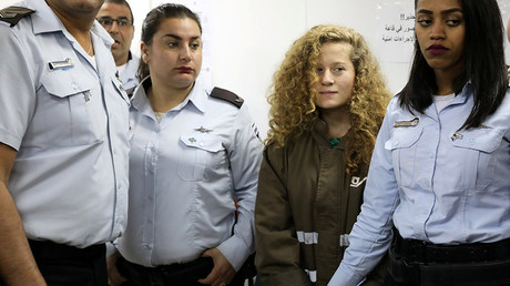 Palestinian teen Ahed Tamimi enters a military courtroom escorted by Israeli Prison Service personnel at Ofer Prison near the West Bank city of Ramallah, December 28, 2017 © Ammar Awad