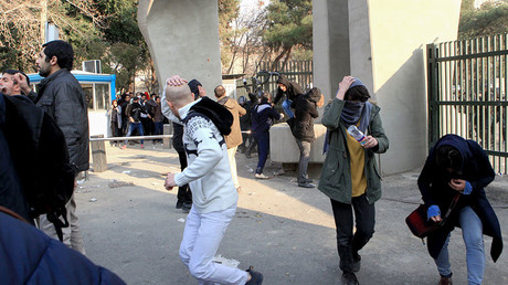 Iranian students run for cover from tear gas at the University of Tehran during a demonstration driven by anger over economic problems, in the capital Tehran on December 30, 2017 © AFP