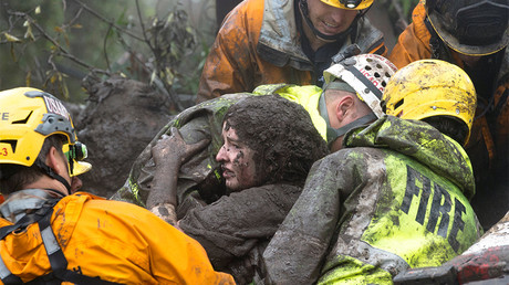 Emergency personnel carry a woman rescued from a collapsed house after a mudslide in Montecito, California, U.S. January 9, 2018 © Kenneth Song