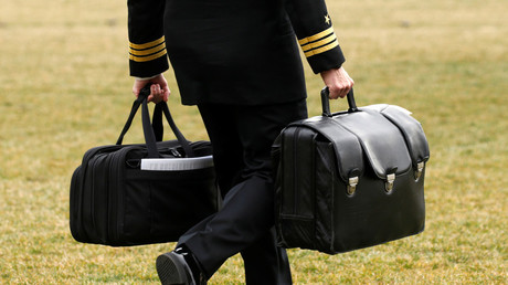 A military aide for US President Donald Trump carries nuclear launch codes © Kevin Lamarque