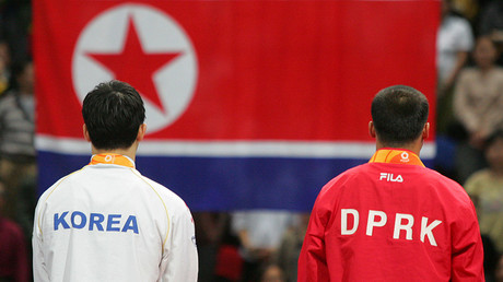 FILE PHOTO: North Korea's gymnast and South Korea's listen to the national anthem as the North Korean flag rises © Claro Cortes