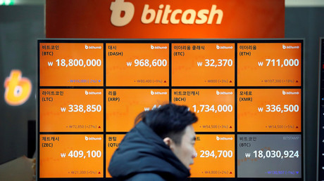 A man walks past an electric board showing exchange rates of various cryptocurrencies including Bitcoin © Kim Hong-Ji