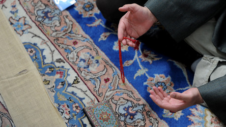 A Muslim prays during a midday prayer at the