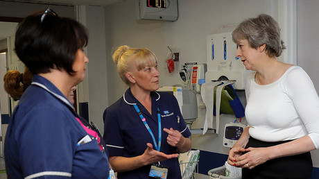 Britain's Prime Minister Theresa May (R) meets nursing staff during her visit to the Renal Transplant Unit at the Royal Liverpool University Hospital in Liverpool. © AFP