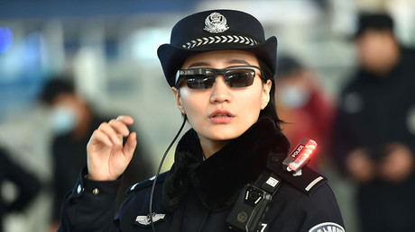 A police officer wearing a pair of smartglasses with a facial recognition system at Zhengzhou East Railway Station. © AFP