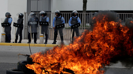 Riot police guard the entrance of Honduras Central Bank as supporters of opposition candidate Salvador Nasralla burn tires during a march to protest against the results of Honduras' general elections in Tegucigalpa, Honduras January 7, 2018. © Jorge Cabrera