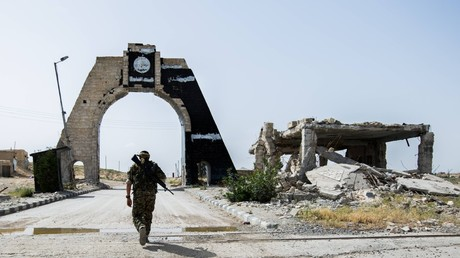 Kurdish fighter in Aleppo province walking toward IS emblazoned arch © imago stock&people