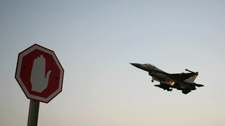 An Israeli Air Force F-16 fighter plane flying above a traffic sign after taking off from an Israeli Air Force Base on July 20, 2006. © Ammar Awad