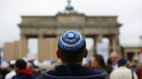 A man wearing a kippah waits for the start of an anti-Semitism demo at Berlin's Brandenburg Gate. © Thomas Peter / Reuters