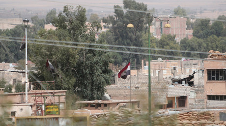 FILE PHOTO Syrian national flags flutter at the governorate building in the northeastern city of Hasaka © Rodi Said