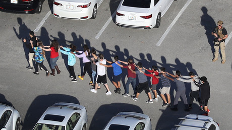 People are brought out of the Marjory Stoneman Douglas High School after a mass shooting. © Joe Raedle / Getty Images North America