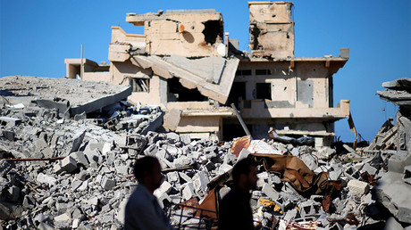 FILE PHOTO: Men walk past the ruins of a building that was destroyed during clashes between Libyan forces and Islamic State militants, in Sirte, Libya © Ahmed Jadallah