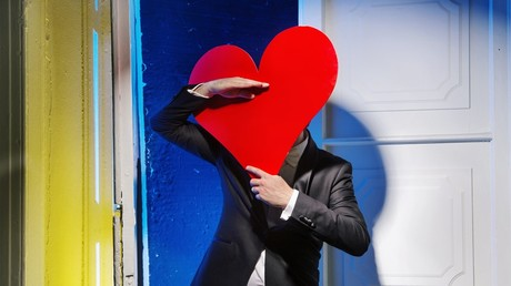 A cheerful man hiding himself behind a big heart.