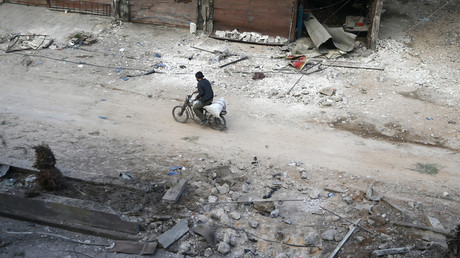 A man rides on a motorbike at a damaged site in the rebel held besieged town of Hamouriyeh, eastern Ghouta, near Damascus, Syria, February 21, 2018. © Bassam Khabieh