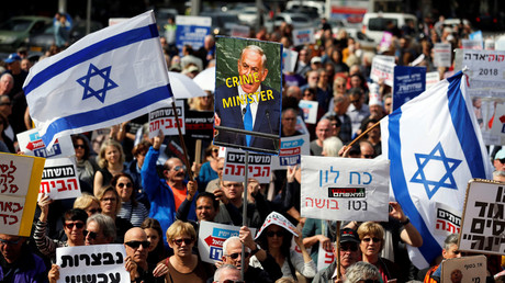Protesters hold signs calling upon Israeli Prime Minister Benjamin Netanyahu to step down. © Amir Cohen