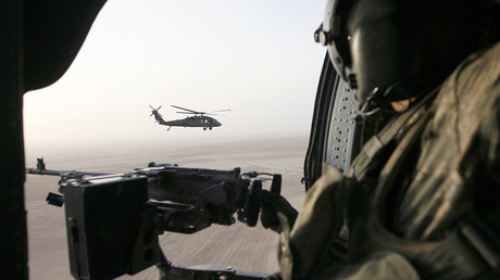 FILE PHOTO: A U.S. soldier holds a machine gun in a U.S. helicopter flying over Samarra, Iraq © Thaier Al-Sudani