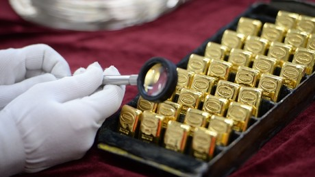 A worker looks at gold bars produced during the opening of a new bank bar manufacturing line at the Yekaterinburg Plant for Non-Ferrous Metals Processing © Pavel Lisitsyn