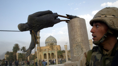 FILE PHOTO: A US soldier watches as a statue of Iraq's President Saddam Hussein falls in central Baghdad, Iraq, on April 9, 2003. © Goran Tomasevic