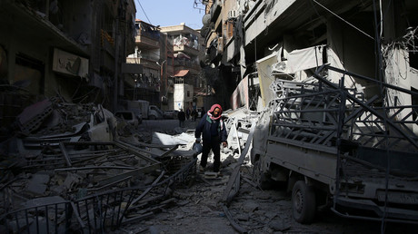 A man walks on the rubble of damaged buildings at the besieged town of Douma, Eastern Ghouta, Damascus. © Bassam Khabieh