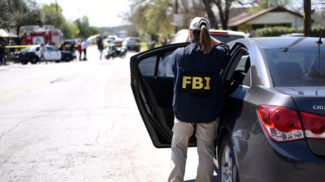 An FBI agent exits her car after arriving at the scene of an explosion near north Galindo street. Police investigators are at the home where a 17-year-old boy was killed and a woman injured in a package bomb explosion in Austin, Texas, U.S., March 12, 2018. Sergio Flores