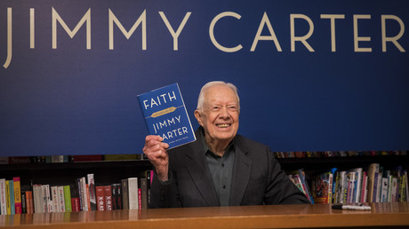 Former U.S. President Jimmy Carter holds up a copy of his new book 'Faith: A Journey For All,' March 26, 2018 in New York City ©  Drew Angerer/Getty Images