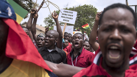 Demonstrators carry banners as they march during a protest in Ghana's capital Accra, March 28, 2018 © Cristina Aldehuela
