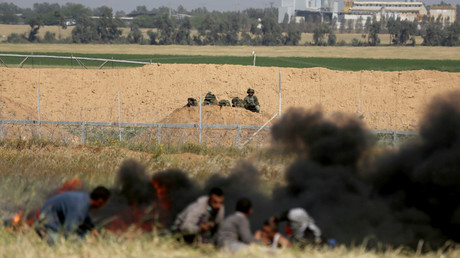 Palestinians take cover from Israeli snipers during clashes at the Gaza-Israel border at a protest demanding the right to return to their homeland, in the southern Gaza Strip March 31, 2018. © REUTERS/Ibraheem Abu Mustafa