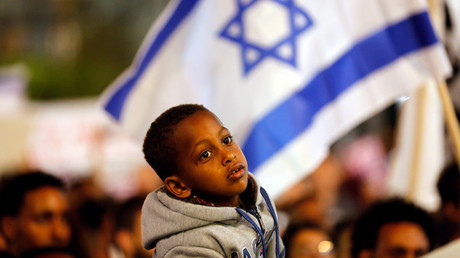 FILE PHOTO: A boy takes part in a protest against the Israeli government's plan to deport African migrants, in Tel Aviv, Israel March 24, 2018. © Corinna Kern
