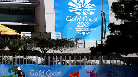 A pedestrian walks past a security fence and barricades located outside a venue for the upcoming Commonwealth Games on the Gold Coast in Australia, April 3, 2018. © David Gray