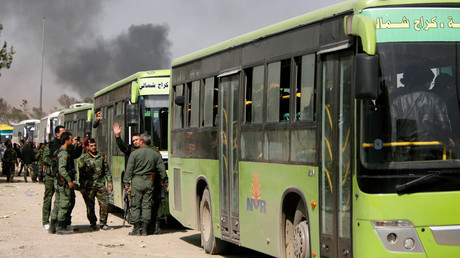 Syrian troops stand next to buses carrying militants and their families before they are evacuated, at Harasta highway outside Jobar, in Damascus, Syria March 25, 2018.  © Omar Sanadiki