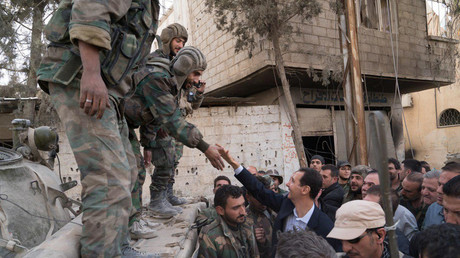 Syrian President Bashar al-Assad reaches out to shake the hand of a Syrian army soldier in eastern Ghouta, Syria, March 18, 2018. © SANA