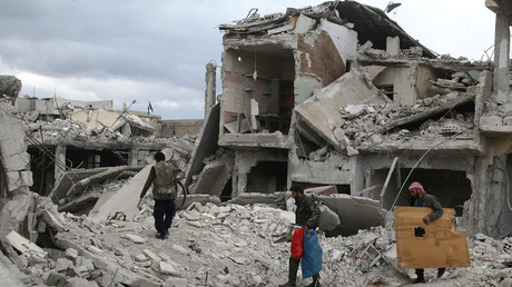 FILE PHOTO: People walk on rubble of damaged buildings in the town of Douma, Eastern Ghouta, Syria © Bassam Khabieh