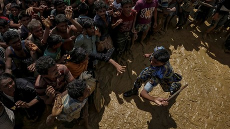 A security officer attempts to control Rohingya refugees waiting to receive aid in Cox's Bazar, Bangladesh © Cathal McNaughton