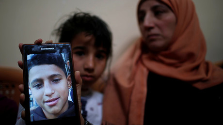 The mother of Mohammed Ayoub shows her son's photo. © Mohammed Salem