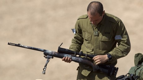 An Israeli army sniper cleans his gun after an exercise in the Negev Desert, January 31, 2012 / JACK GUEZ