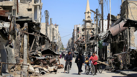 People walk down a damaged street in Douma, Syria. © Ali Hashisho / Reuters