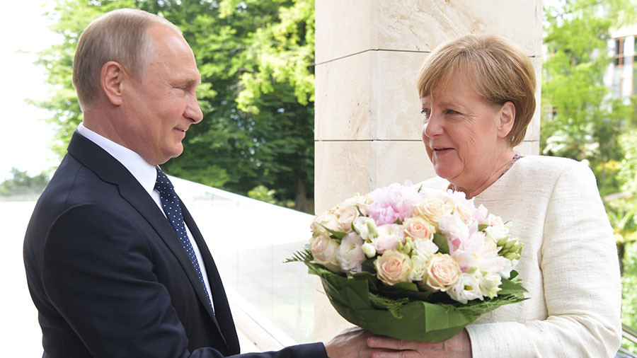 Flower power: Putin greets visiting Merkel with bouquet (VIDEO)