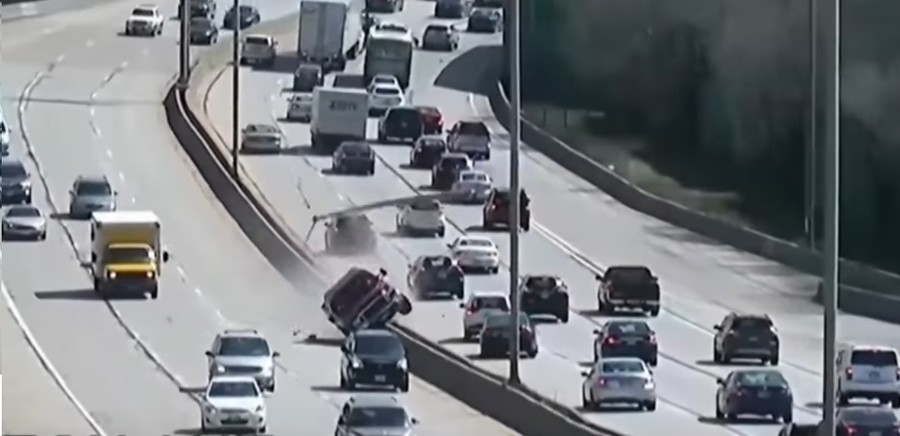 Careening truck knocks into two highway poles & sends them flying into traffic (VIDEO)