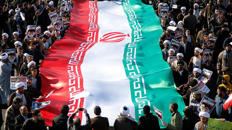 Pro-government demonstrators wave their national flag during a march in the Iranian city of Qom on January 3, 2018. © Mohammad Ali Marizad