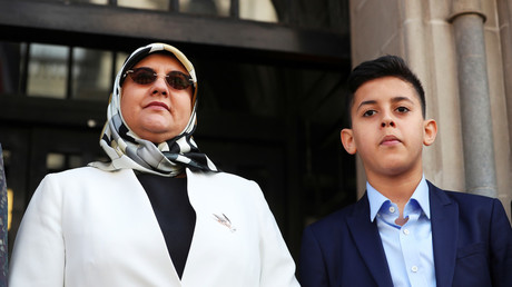 Hakim Belhadj's wife Fatima Boudchar, with their son Abderrahim who Boudchar was pregnant with at the time of her abduction and imprisonment, outside Parliament to hear the AG's apology. © Hannah McKay
